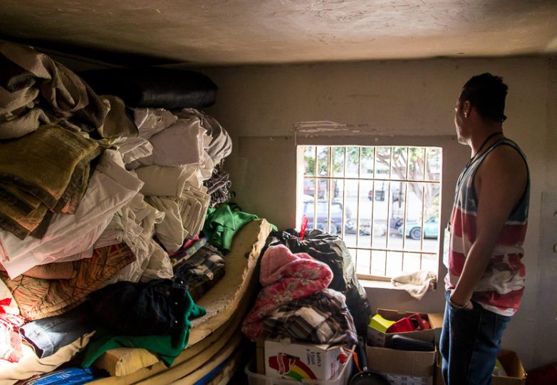 Pedro Alberto Cordova, manager of Hotel Migrante, looks out the window from the facility's second floor donation storage room. A shelter for men who are deported or in transit, it has recently begun welcoming some families due to an increase of need for shelter space, February 28, 2019. Photo: Mabel Jiménez