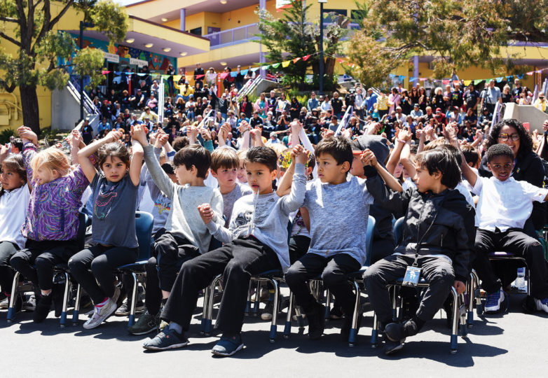 """Students at Dolores Huerta Elementary School hold hands and get ready to chant """"Si se puede"""" on May 17, 2019. Photo: Alejandro Galicia Diaz"""