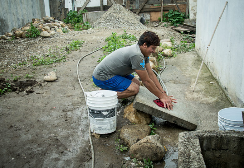 Alexis washes clothes by hand against a concrete slab. Alexis arrived to Tijuana just two nights before with a recent migrant caravan and all new residents of Casa de Luz shelter are busy with cleanup and repair projects. Photo: Mabel Jiménez