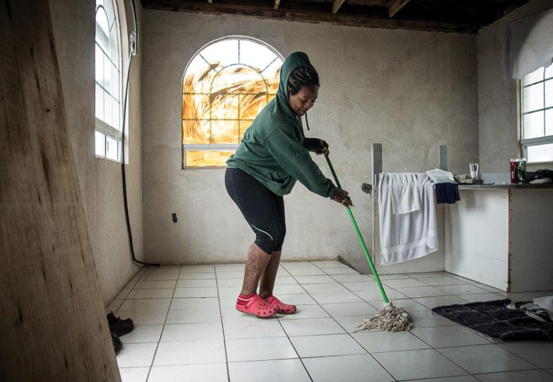 Sharon limpia una gotera en Casa de Luz, un nuevo refugio para migrantes LGBT en Tijuana, el lunes 11 de marzo de 2019. Siendo mujer trans, huyó de Honduras después de que su padre tratara de matarla y espera buscar asilo en los EEUU. Foto: Mabel Jiménez