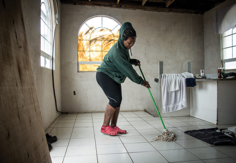 A migrant named Sharon mops a puddle from a leaky roof at Casa de Luz, a new LGBT friendly migrant shelter in Tijuana, March 11, 2019. A trans woman, Sharon fled Honduras after her transphobic father tried to kill her. She hopes to gain asylum in the United States. Photo: Mabel Jiménez