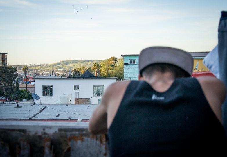 Jenri Jose Juarez Villegas, a 16-year-old migrant from El Salvador at Jardin de las Mariposas, a rehab center for the LGBT community, March 15, 2019. Juarez, who escaped gang threats in El Salvador, looks at a patch of green U.S. soil visible amongst the Tijuana skyline. Photo: Mabel Jiménez