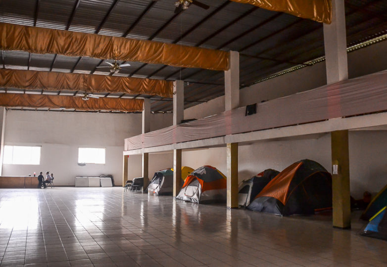 Living tents are set up in the largest room of the main building at Embajadores de Jesus church and community, on February 26, 2019 in the Cañon del Alacrán neighborhood of Tijuana, Mexico. The tents share the room with a stage and chairs where community members attend mass. Photo: Mabel Jiménez