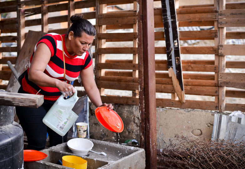 A woman who arrived in one of the recent Central American caravans washes dishes in front of Embajadores de Jesus church, also known as Little Haiti, in the Cañón del Alacrán neighborhood in Tijuana, México, February 27, 2019. While the community was established to house Haitian families, it has recently begun receiving a Central American population as well. Photo: Mabel Jiménez