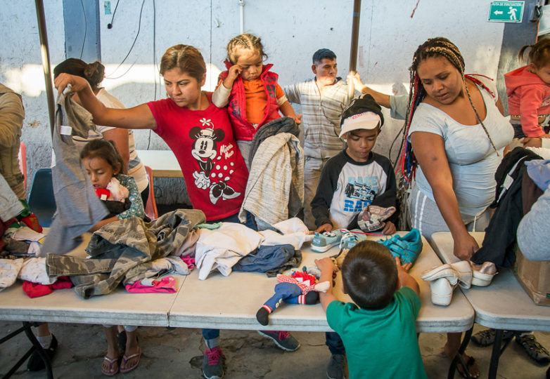 Families search through recently arrived donations at Roca de Salvacion shelter, March 14, 2019. One of the most remote migrant shelters in Tijuana, it is located at the foot of El Cerro Colorado mountain, in the Cañón de la Raza neighborhood. Photo: Mabel Jiménez