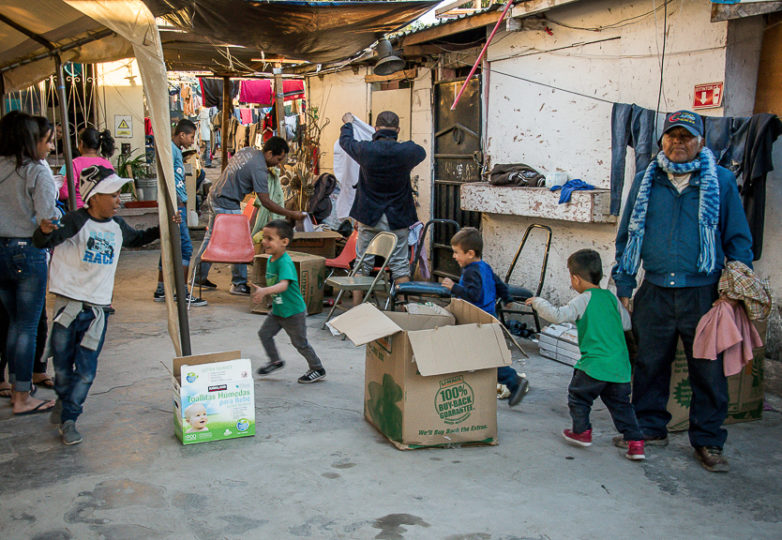 Children play near recently arrived donation boxes at Roca de Salvacion shelter, March 14, 2019. One of the most remote migrant shelters in Tijuana, it is located at the foot of El Cerro Colorado mountain, in the Cañón de la Raza neighborhood. Photo: Mabel Jiménez