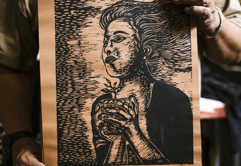 """Txutxo Perez en su estudio ubicado en el Edificio Redstone en el Distrito Misión, sostiene una impresión en serigrafía en la que se lee """"La Resistencia es Fértil"""". Foto: Dane Pollok"""