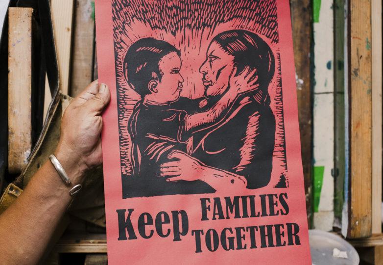 """Txutxo Perez en su estudio en el Edificio Redstone en la Misión, sostiene el grabado """"Mantener las familias juntas"""". Foto: Dane Pollok"""