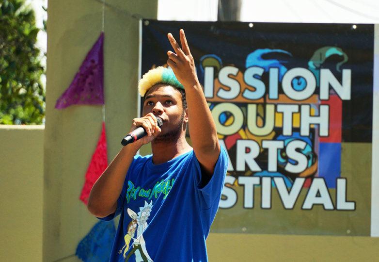 Un MC del Proyecto DJ habla sobre los problemas enfrentados al ser criado en el sistema de adopción, durante el Festival de Artes Juveniles de la Misión en el Parque La Raza en San Francisco.
