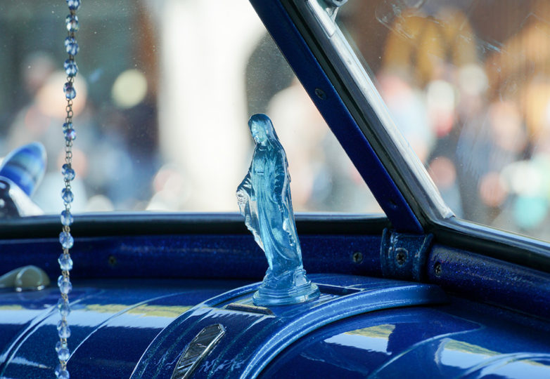 A decorative religious ornament sits on the dashboard of a lowrider at the King of the Streets contest pose for a portrait in their lowrider at City College of San Francisco on July 13, 2019. Photo: Iván Hernández