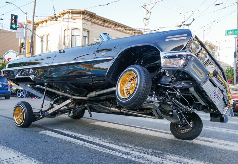 A lowrider parked on three wheels on Mission Street shows off at the annual King of the Streets event, presented by The San Francisco LowRider Council, on July 13, 2019. Photo: Iván Hernández